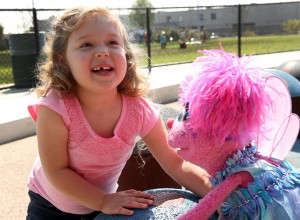 Girl playing with Abby Cadabby on a playground