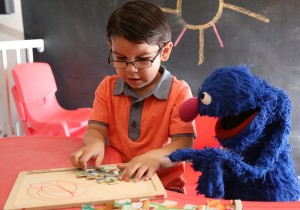 A boy plays with a puzzle while Grover helps